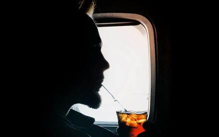 man enjoying a drink in an airplane